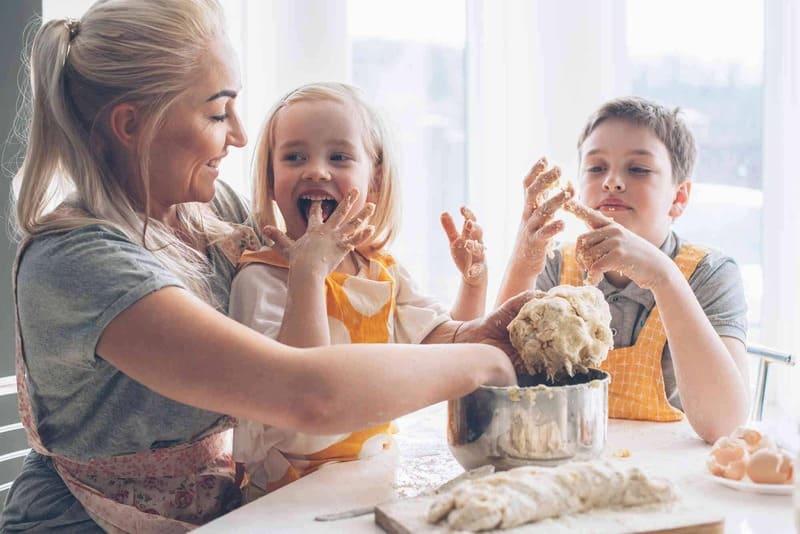Mamãe cozinheira fazendo pão com o casal de filhos