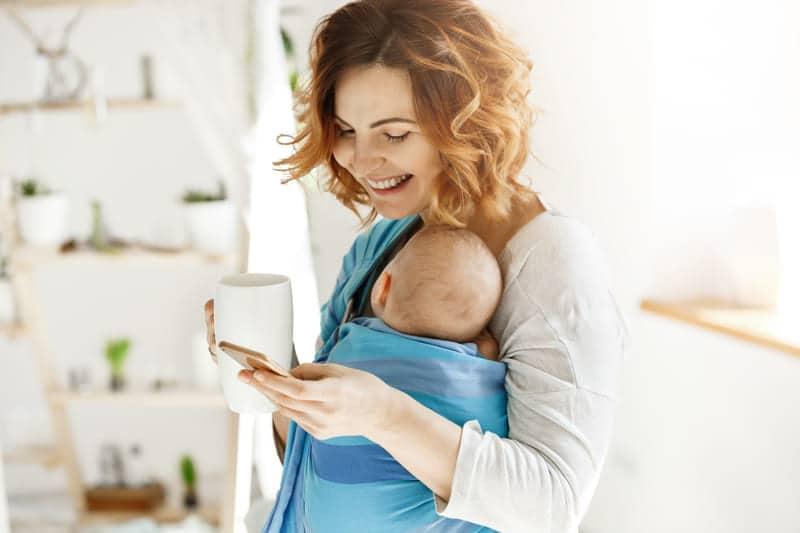Mamãe com o seu bebê no sling azul