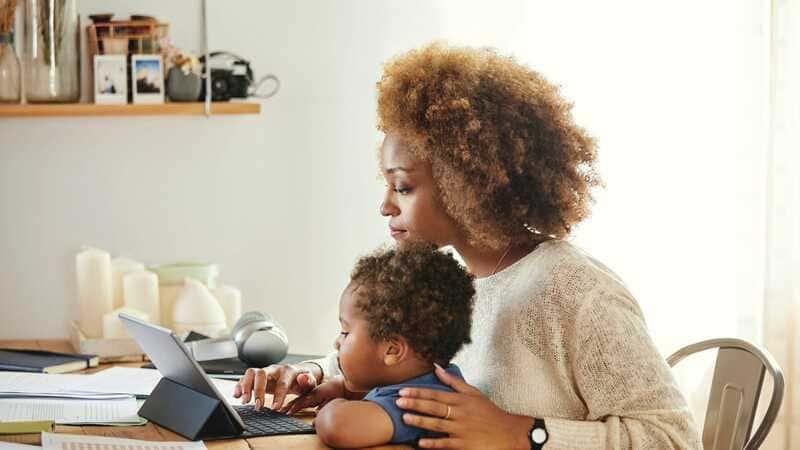 Mamãe workaholic trabalhando no computador com o filho no colo